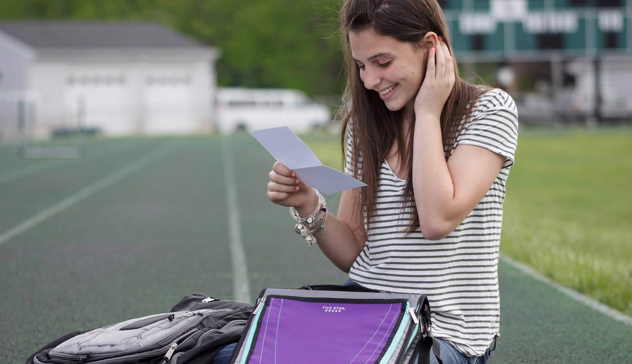 natural smile real girl smiling holding binder notes school branded UGC content shirt stripes